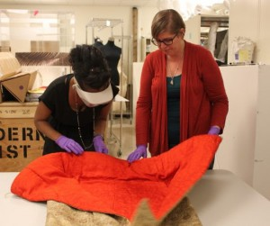 Keidra Daniels Navaroli, left, assistant director and curator at the Ruth Funk Center for Textile Arts, and Director of Collections Sarah Smith inspect an item from the center's permanent collection.